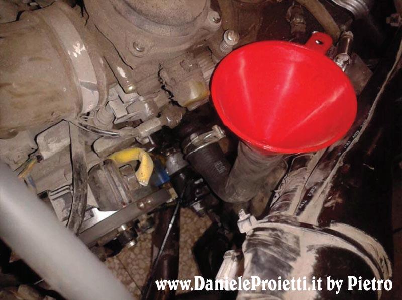 [foto n° 2 - inserimento acqua nel cilindro tramite imbutino rosso]